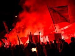 Fackelzug mit zugeklebten Mündern: Die Befürworter eines Wechsels von Moutier zum Kanton Jura sehen die Demokratie verletzt. (Bild: KEYSTONE/JEAN-CHRISTOPHE BOTT)