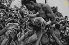 Bei dem Charak Puja Festival werden Gläubige an einen Haken gehängt, diese schmerzhafte Prozedur soll ihre Kinder vor Ängsten befreien. (Bild: National Geographic/Avishek Dasy)