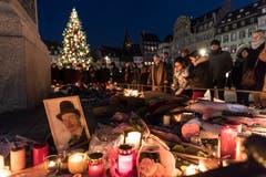 Menschen legen Blumen und Kerzen nieder in Strassburg. (Bild: AP Photo/Jean-Francois Badias, Pool, 14. Dezember 2018)