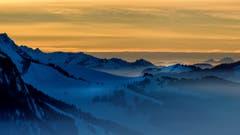 Nebelverhangene Hügellandschaft im Toggenburg mit einem brennenden Himmel im Hintergrund. (Bild: Reto Schläpfer)