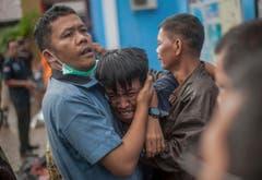 Ein Mann, der gerade einen Angehörigen identifiziert hat. (Bild: Fauzy Chaniago/AP (Carita, 23. Dezember 2018)