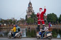 Ein gigantischer Weihnachtsmann schwimmt auf dem See vor der Phu-My-Kathedrale ausserhalb der Vietnamesischen Hauptstadt. In Vietnam, einem hauptsächlich buddhistischen Land, ist das Weihnachtsfest zwar keinem offiziellen Feiertag gleichgesetzt, trotzdem wird es vielerorts gefeiert. (Bild: Linh Pham/Getty (Hanoi, 23. Dezember 2018))