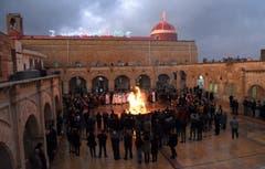 Irakische Christen versammeln sich um ein Feuer während der Weihnachtsabend-Prozession in der Nähe von Mosul. (Bild: EPA/AMMAR SALIH, 24. Dezember 2018)