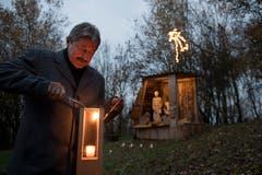 Alois Muri, Gemeindepräsident von Gisikon, zündet eine Laterne an. (Bild: Corinne Glanzmann; 30. November 2018)
