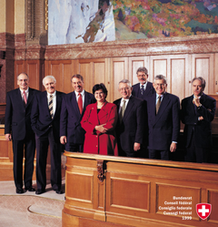 1999, Bild 1 (von links): Pascal Couchepin, Flavio Cotti, Adolf Ogi, Bundespräsidentin Ruth Dreifuss, Arnold Koller, Bundeskanzler François Couchepin, Kaspar Villiger, Moritz Leuenberger.