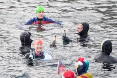 Ein Prosit mit alkoholfreien Getränken: Am Silvester-Schwimmen in der Reuss. (Bild: KEYSTONE/Urs Flüeler; Luzern, 31. Dezember 2018)