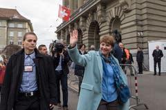 Die neugewaehlte Bundesraetin Viola Amherd, rechts, neben einer Polizistin, winkt vor dem Bundeshaus nach der Ersatzwahl in den Bundesrat durch die Vereinigte Bundesversammlung. (Bild: KEYSTONE/Anthony Anex)