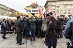 Sicherheits- und Medienleute umkreisen auf dem Bundesplatz in Bern die neugewählten Bundesrätinnen beim Bad in der Menge. (Bild: KEYSTONE/Anthony Anex)