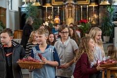 Die Fünftklässler verteilen nach ihren Aufführungen in der Kirche Rain rote Pakete an die Senioren.Bild: Nadia Schärli (4. Dezember 2018)