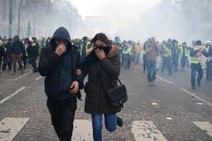 Ein Demonstrant und eine Demonstrantin auf der Flucht. (Bild: Rafael Yaghobzadeh/AP Photo (Paris, 08.12.2018))