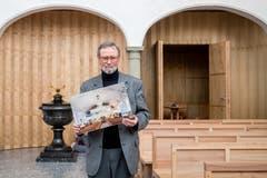 Hansruedi Kleiber, leitender Priester Peterskapelle, in der renovierten Peterskapelle. Er trägt ein Bild von der Kirche vor ihrer Sanierung. (Bild: Philipp Schmidli, 7. Dezember 2018)
