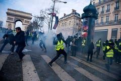 Die Gelbwesten kämpfen gegen die Polizeikräfte. Hier schleudert ein Demonstrant ein rauchendes Objekt. (Bild: Julien de Rosa/EPA (Paris, 08.12.2018))