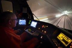 Er drückt den Hebel nach vorne: Der Lokführer im Cockpit des Testzugs während einer Fahrt durch die Weströhre von Erstfeld nach Biasca. (Bild: KEYSTONE/GAETAN BALLY)
