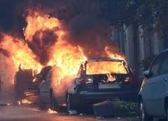 Autos auf den Strassen Mailands brennen lichterloh, nachdem die italienische Polizei und die Demonstranten aneinander gerieten. (Bild: DANIEL DAL ZENNARO)