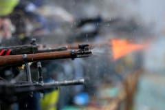 Eine Stichflamme aus einem Gewehr eines Rütlischützen. (Bild: Keystone)