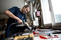Mitarbeiter Bruno Egli bezieht das Sattelgestell mit Leder. (Bild: Corinne Glanzmann / Neue LZ)