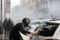 Ausnahmezustand in Mailand: Ein Aktivist schlägt mit einem Gegenstand die Scheibe eines parkierten Autos ein. (Bild: MASSIMO PERCOSSI)