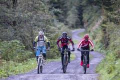 Sie sind mit dem Velo unterwegs: René Zimmermann, Reto und Linda Indergand (von links). (Bild: Keystone / Alexandra Wey)