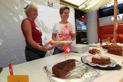 An der 1. August-Feier in Beckenried. Wisi Imholz (links) übergibt Peter Mathis die Fischspezialität. nes Murer (links) und Heidi Scheuber verkaufen Kuchen. (Bild: Roger Zbinden / Neue NZ)