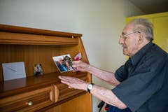 Ferdinand Wyss macht es sich heimelig im neuen Zuhause – und rückt das Foto von sich und seiner verstorbenen Freundin an den richtigen Platz. (Bild: Roger Grütter / Neue LZ)