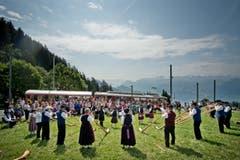 Auf dem Bild zu sehen ist das Alphornensemble mit Pipes und Drums vor der einfahrenden Rigi-Bahn. (Bild: Pius Amrein (Neue LZ))