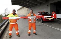 Der Verantwortliche des Kantons Uri, Werner Gnos (links) und sein Tessiner Assistent Alfio Curti, öffnen eine Barriere oberhalb von Airolo. (Bild: Keystone)