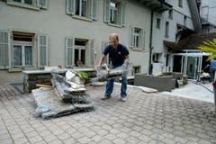 Mitarbeiter der Bäckerei Brunner sind auch eineinhalb Wochen nach der Verwüstung mit Aufräumarbeiten beschäftigt. (Bild: Dominik Wunderli (Neue LZ))