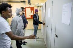 Asylbewerber zeigen die Duschen in der Asyl-Notunterkunft. (Bild: Philipp Schmidli)