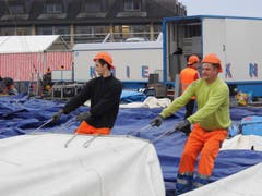 Harte Arbeit für ein kurzes Gastspiel: Arbeiter legen die riesigen Zeltplanen aus. (Bild: Martin Mühlebach / Neue ZZ)