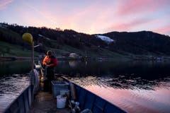 Auf den gelben Ball auf dem Boot von Hanspeter Merz – das Zeichen für Berufsfischer – fällt das erste Tageslicht. (Bild: Alexandra Wey/Keystone (Ägeri, 22. November 2017))