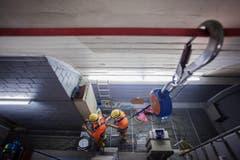 Zwei Arbeiter sichern sich während des Abtransports eines Lüftrades der Belüftungsanlage. (Bild: Keystone)