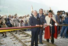 Bundesrat Leon Schlumpf, Vorsteher des Eidgenössischen Verkehrs- und Energiewirtschaftsdepartementes, durchtrennt am 25. Juni 1982 in Oberwald das Band und eröffnet feierlich den Furkatunnel. (Bild: Keystone / Str)
