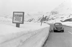 """Ein VW-Käfer passiert auf der Passstrasse ein Strassenschild, welches die Passhöhe am Lukmanier in der italienischen Schreibweise: """"Lucomagno"""" ankündigt, aufgenommen am 2. Mai 1972. Der Lukmanier verbindet das bündnerische Vorderrheintal mit dem Tessiner Bleniotal. (Bild: Keystone)"""