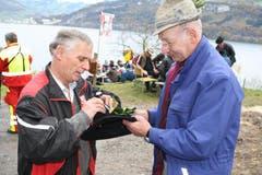 Otto Waser (rechts) vom Seelisberg verteilt seit gut 40 Jahren Stechpalmen als Hutschmuck für die Hüte. (Bild: Irene Infanger / Neue SZ)