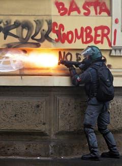 Ein italienischer Polizist feuert mit Tränengas auf die maskierten Demonstranten. (Bild: MASSIMO PERCOSSI)