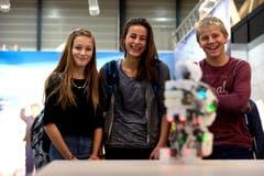 Luisa Pfyl, Julia Wigget und Oliver Schuler amüsieren sich an der Zentralschweizer Bildungsmesse Zebi auf der Luzerner Allmend an einem Roboter. (Bild: Nadia Schärli / Neue LZ)