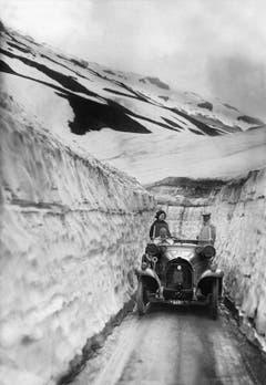 Ein Auto fährt im Frühsommer 1914 durch den Schneekorridor der Klausenpasshöhe entgegen. (Bild: Keystone)