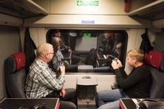 Zwei Premiere-Passagiere sehen nichts durchs Fenster. Da bleibt Zeit für Grüsse aus dem Tunnel. (Bild: Keystone / Epa / Christian Beutler)