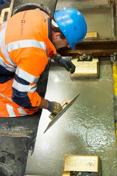 Arbeiter Helmut Fortschegger reibt mit einem goldigen Brett die Beton Schicht im längsten Eisenbahntunnel der Welt glatt. (Bild: SIGI TISCHLER)