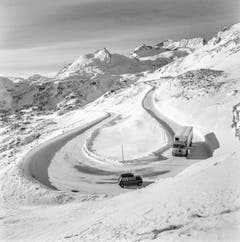 Zwei Fahrzeuge kreuzen sich auf der Südseite am Berninapass, unterhalb der Alp Grüm auf einer Strassenkehre bei winterlichen Verhältnissen, aufgenommen im Dezember 1969. (Bild: Keystone)