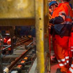 Arbeiter reiben mit einem goldigen Brett die Beton Schicht im längsten Eisenbahntunnel der Welt glatt. (Bild: SIGI TISCHLER)