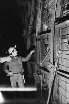 Tunnelarbeiter im Furkatunnel zeigen am 11. Dezember 1977 auf Seitenverstrebungen, die vom Felsdruck ins Innere des Tunnels gedrückt werden. Dies ist ein Grund für die Bauverzögerungen, die zur Folge hat, dass der Tunnel 80 Millionen Franken teurer wurde als geplant. (Bild: Keystone / Str)