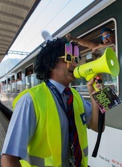 Ein mit Perücke und Brille verkleideter Zugführer der SBB gibt das Abfahrtssignal für den Street-Parade-Extrazug von Lugano nach Zürich. (Bild: Keystone)