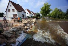 Hausbesitzer schützen sich mit Sandsäcken vor den Fluten. (Bild: Keystone)