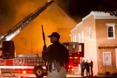 Ein Polizeioffizier steht in der Nähe eines Brandplatzes. (Bild: AP Photo/Matt Rourke)