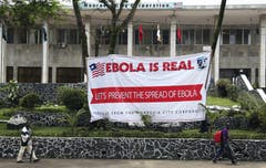 """Ebola-Hinweisschilder im westafrikanischen Liberia. """"Ebola ist real. Lasst uns gemeinsam die Ausbreitung von Ebola bekämpfen!» steht darauf geschrieben. (Bild: Keystone)"""