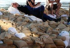 Helfer ruhen auf den Sandsäcken aus. (Bild: Keystone)