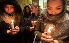 Frauen mit Kerzen vor der französischen Botschaft in Montreal. (Bild: AP/Graham Hughes)