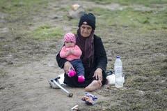 Die Regenfälle haben den Boden in Idomeni, auf welchem auch diese Frau und das Baby leben, in Schlamm verwandelt. (Bild: Keystone)