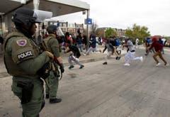 Demonstranten rennen vor Polizisten davon. (Bild: AP Photo / Jose Luis Magana)